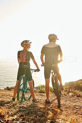 Buy stock photo Shot of a young couple admiring the view from a hilltop while out on a bike ride