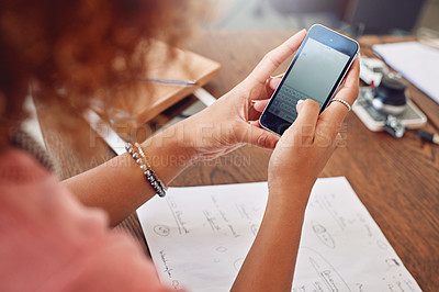 Buy stock photo Cropped shot of a young designer using her cellphone at the office
