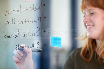 Buy stock photo Cropped shot of a young woman creating a plan on glass in a modern office
