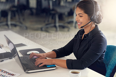 Buy stock photo Shot of a call centre agent sitting at her desk in a modern office
