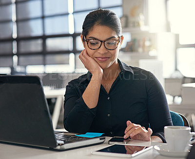 Buy stock photo Shot of a business woman using her phone while working at her desk