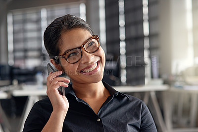 Buy stock photo Shot of a young businesswoman talking on her phone at the office