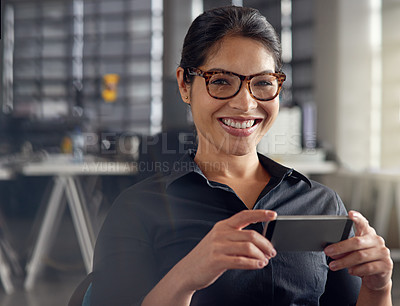 Buy stock photo Shot of a young businesswoman using her cellphone at the office
