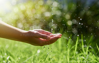 Buy stock photo Shot of hands held out to catch a stream of water outside