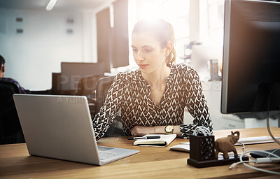 Buy stock photo Shot of a young woman using a laptop at her desk in a modern office