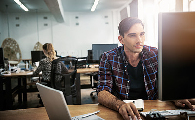 Buy stock photo Shot of a young man using a computer at his desk in a modern office
