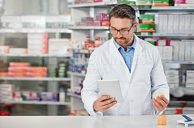 Buy stock photo Shot of a pharmacist doing some research on a digital tablet. All products have been altered to be void of copyright infringements