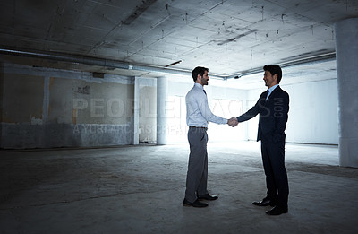 Buy stock photo Full length shot of two professional architects shaking hands on a construction site