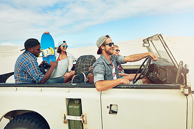 Buy stock photo Shot of a group of young friends going on a sand boarding road trip in the desert