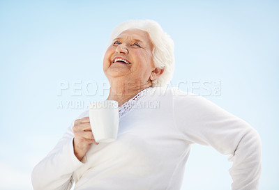 Buy stock photo Low angle shot of a laughing senior woman holding a cup of coffee