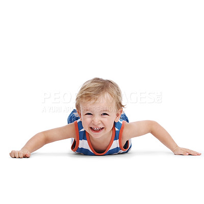 Buy stock photo Portrait of a cute little boy lying on floor and smiling isolated against white background
