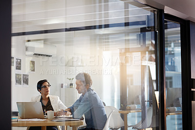Buy stock photo Shot of businesspeople working on a laptop in an office