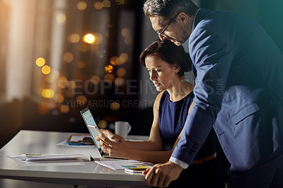 Buy stock photo Shot of a coworkers using a smartphone while woking late in the office