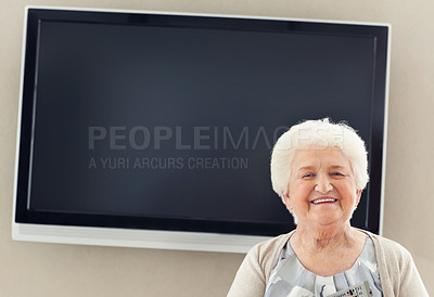 Buy stock photo A portrait of a senior woman standing with a huge TV behind her - copyspace
