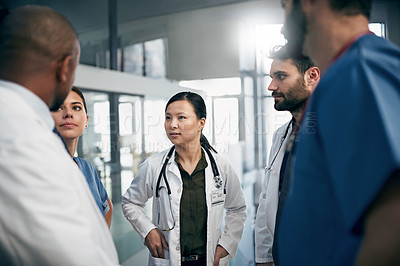 Buy stock photo Shot of a diverse team of doctors having a discussion
