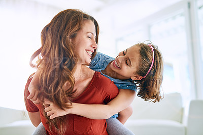 Buy stock photo Cropped shot of a mother giving her daughter a piggyback ride at home