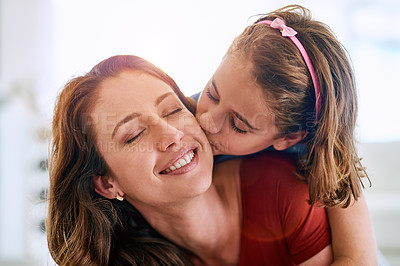 Buy stock photo Cropped shot of a young girl giving her mother a kiss on the cheek at home