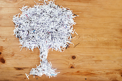 Buy stock photo Studio shot of shredded paper arranged in the shape of a tree on a wooden table