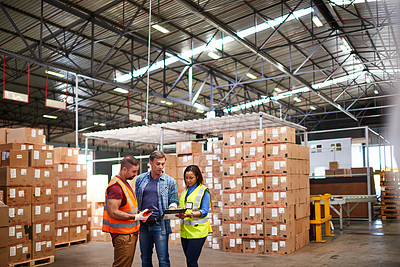Buy stock photo Shot of a group of coworkers talking together while standing in a large warehouse full of boxes