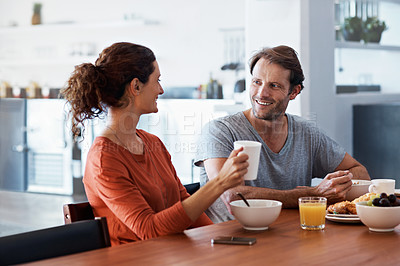 Buy stock photo Shot of a content couple enjoying breakfast together at home
