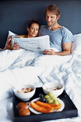 Buy stock photo Shot of content couple reading the paper together and having breakfast in bed
