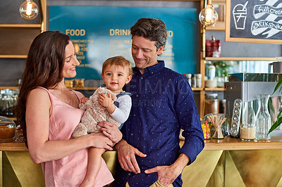 Buy stock photo Portrait of a smiling couple and their little girl standing in their bakery