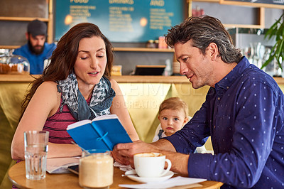 Buy stock photo Shot of a couple and their baby daughter sitting at a table in a cafe