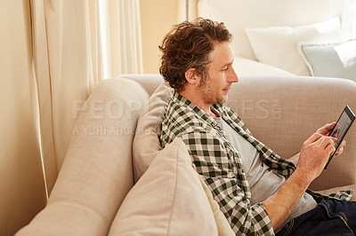 Buy stock photo Cropped shot of a man using his digital tablet at home