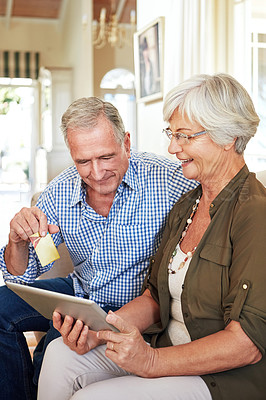 Buy stock photo Cropped shot of a senior couple shopping online on their tablet