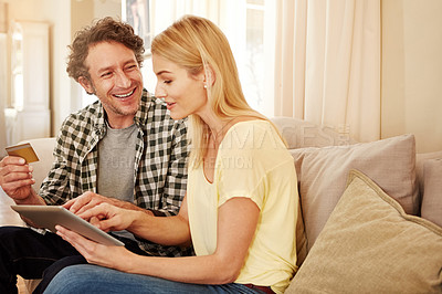 Buy stock photo Cropped shot of a loving couple shopping online on their tablet