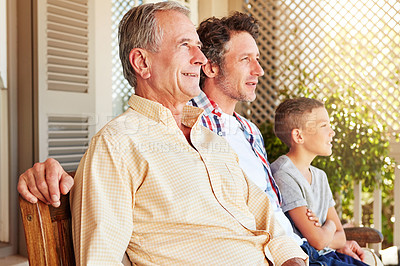Buy stock photo Cropped shot of a young boy sitting outside with his father and grandfather