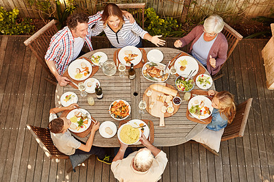 Buy stock photo High angle shot of a family eating lunch outdoors