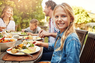 Buy stock photo Portrait of a happy little girl enjoying an outdoor lunch with her family