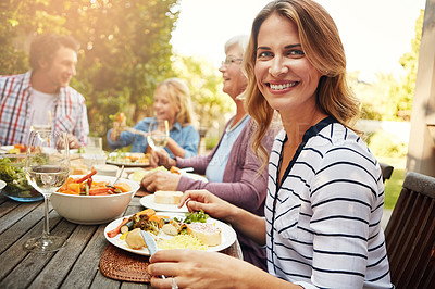 Buy stock photo Portrait of a happy woman enjoying an outdoor lunch with her family