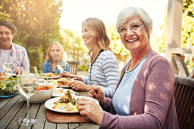 Buy stock photo Portrait of a happy elderly woman enjoying an outdoor lunch with her family