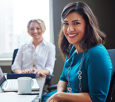 Buy stock photo Portrait of two businesswomen having a meeting together in an office