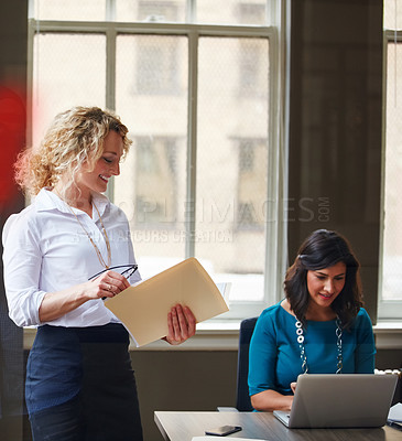 Buy stock photo Shot of a businesswoman going over paperwork in an office