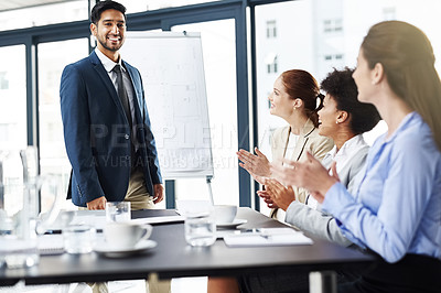 Buy stock photo Shot of a group of businesspeople applauding their colleague's presentation