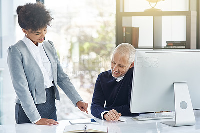 Buy stock photo Shot of a young businesswoman showing her colleague something on a tablet