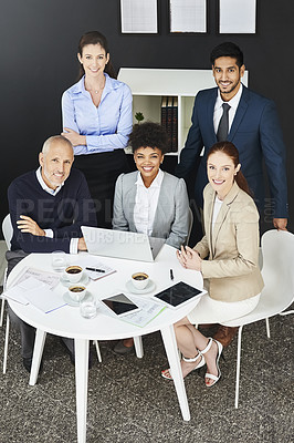 Buy stock photo Shot of a group of businesspeople gathered around a round table