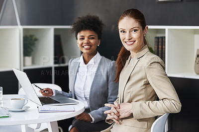 Buy stock photo Cropped shot of two businesswomen seated at a table with a laptop