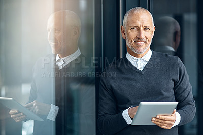 Buy stock photo Shot of a mature businessman using his digital tablet at the office