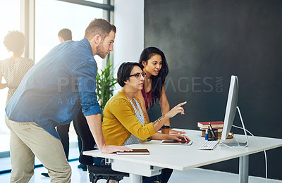 Buy stock photo Cropped shot of a group of colleagues working together on a computer in a modern office