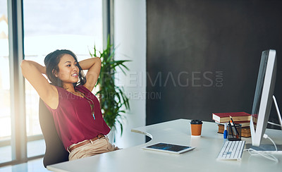 Buy stock photo Cropped shot of a young businesswoman relaxing at her desk in a modern office