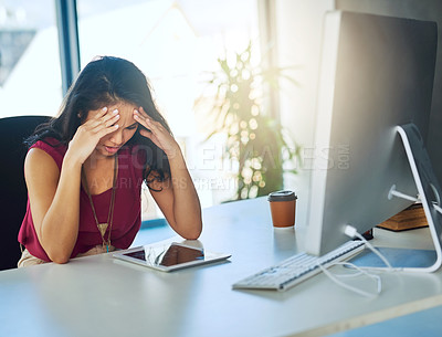Buy stock photo Cropped shot of a young businesswoman looking stressed out at her desk