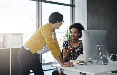 Buy stock photo Cropped shot of two young businesswomen working together in a modern office