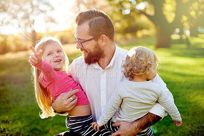 Buy stock photo Shot of a father and his young daughters spending time together at the park