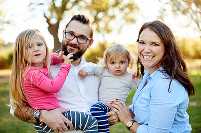 Buy stock photo Portrait of a family of four enjoying a sunny day at the park
