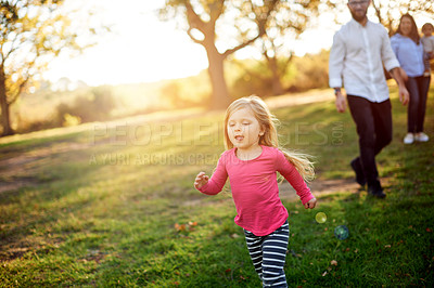 Buy stock photo Shot of an adorable little girl playing in the park while her parents look on in the background