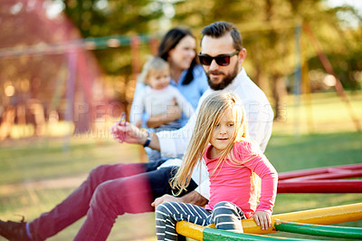 Buy stock photo Cropped shot of a young family sitting on a merry go round in the park
